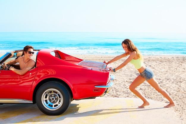 Meisje dat een gebroken auto op de strand grappige kerel duwt