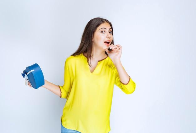 Meisje dat een geschenkdoos in de vorm van een blauwe hartvorm vasthoudt en iemand belt om het te presenteren.