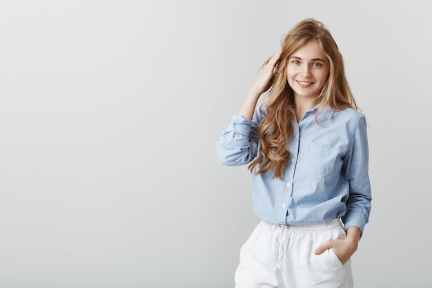 Meisje dat een gewone babbel heeft met vrienden. charmante jonge blanke vrouwelijke blonde in blauwe blouse, haar aanraken en vrolijk glimlachen, beleefd zijn met de klant tijdens het werk op kantoor