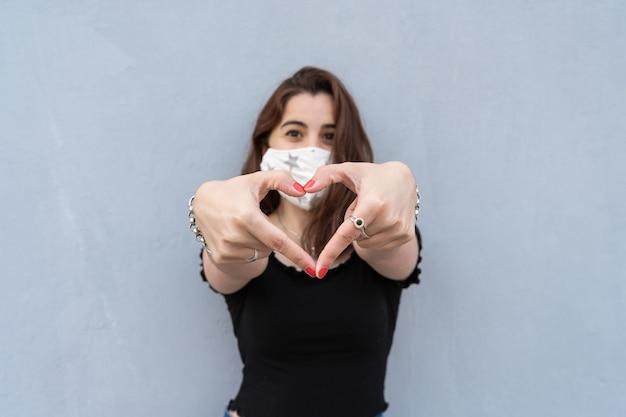 Meisje dat een gezichtsmasker gebruikt en een hartvorm maakt met haar handen. concept van bescherming en liefde.
