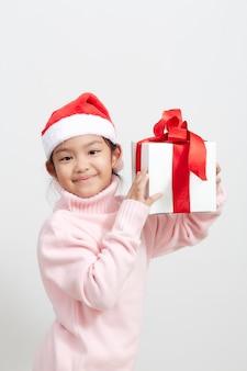 Meisje dat een giftdoos in sweater en santahoed houdt