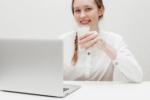 Meisje dat een glas melk houdt terwijl het kijken op haar laptop