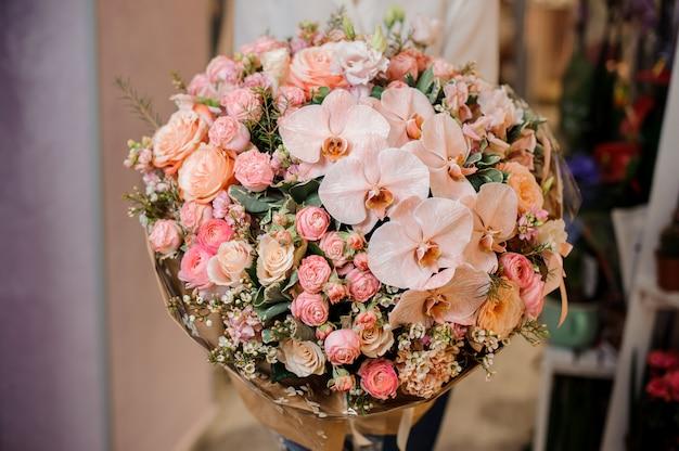 Meisje dat een groot mooi boeket van orchidee en rozen houdt