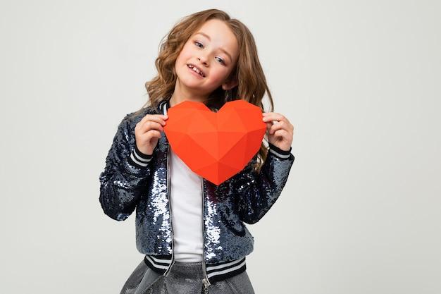 Meisje dat een groot rood 3d hart houdt dat van document op een lichte muur wordt gemaakt