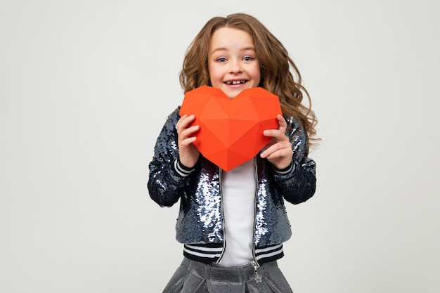 Meisje dat een groot rood hart houdt dat van document op een lichte muur wordt gemaakt