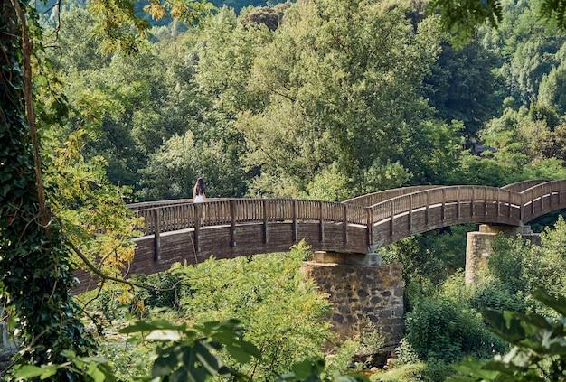 Meisje dat een houten brug oversteekt
