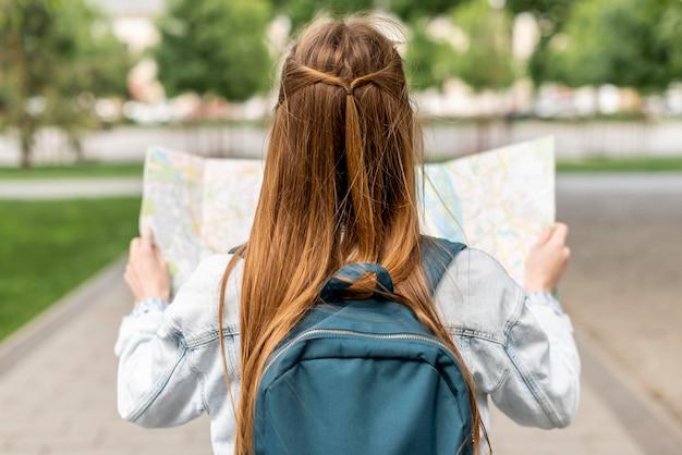 Meisje dat een kaart van achter schot bekijkt