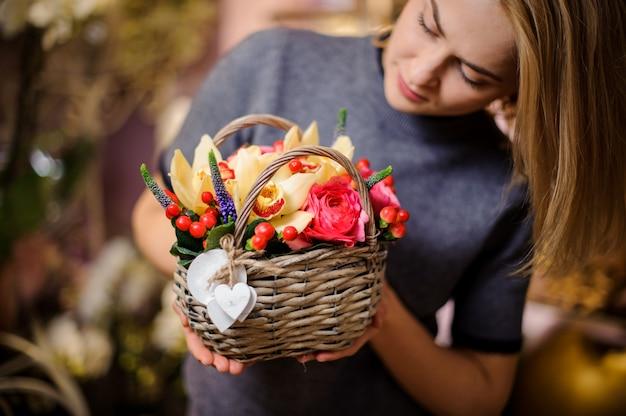 Meisje dat een kleine mand van de lentebloemen houdt