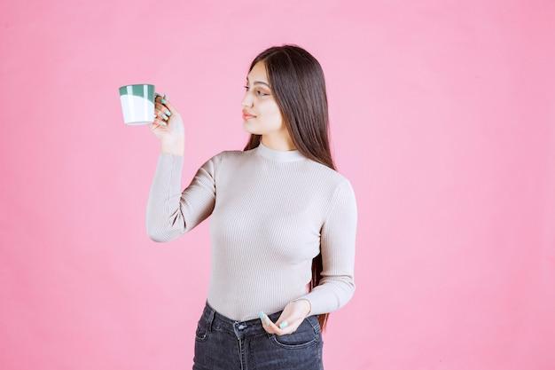 Meisje dat een koffiemok van de witgroene kleur houdt en zich positief voelt