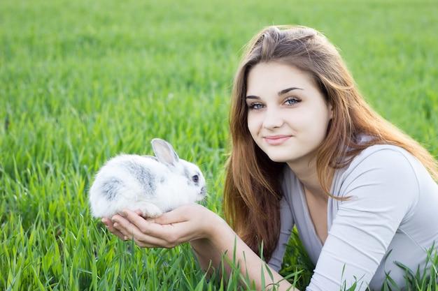 Meisje dat een konijn houdt terwijl op een groene weide.