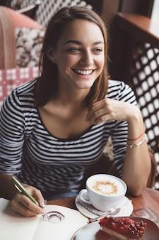 Meisje dat een kop van koffie in het notitieboekje trekt