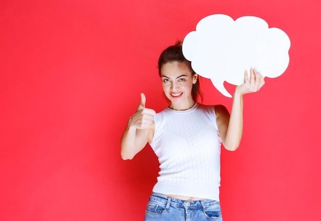 Meisje dat een leeg ideaboard in de vorm van een wolk houdt en ervan geniet.
