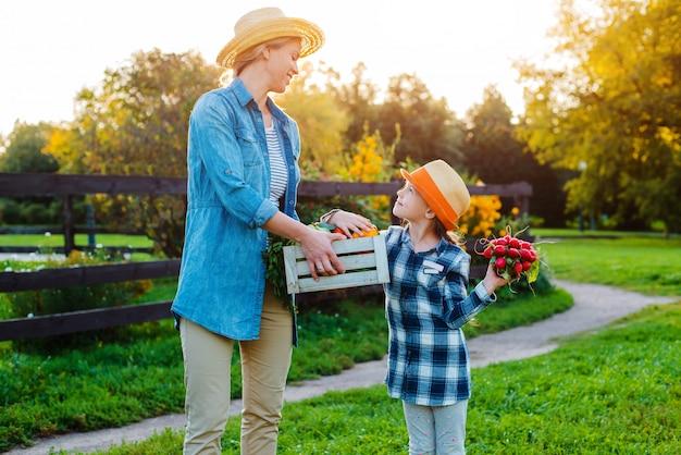 Meisje dat een mand verse organische groenten met haar mamma houdt