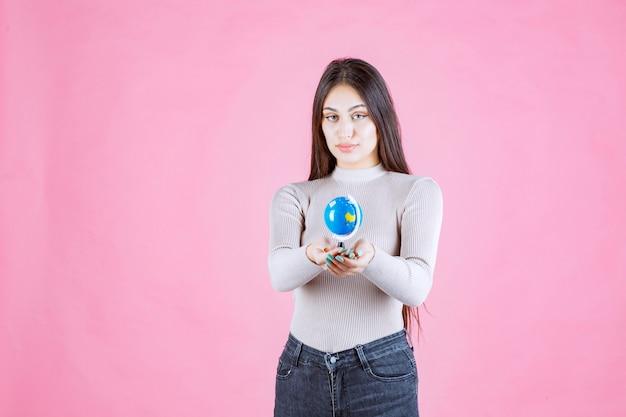 Meisje dat een minibol houdt en glimlacht