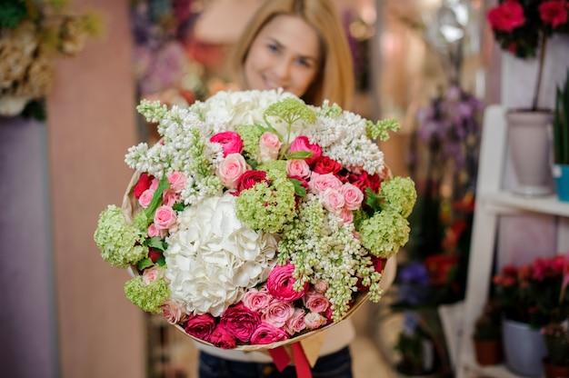 Meisje dat een mooi boeket van magnolia's en rozen houdt