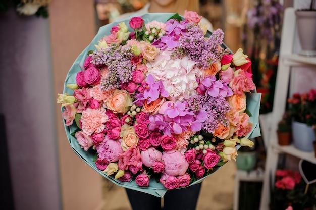 Meisje dat een mooi boeket van orchideeën, rozen en een andere bloemen houdt