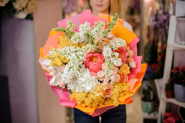Meisje dat een mooi boeket van witte seringen en rozen houdt