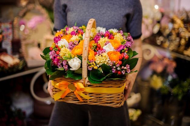 Meisje dat een mooie mand van de lentebloemen houdt