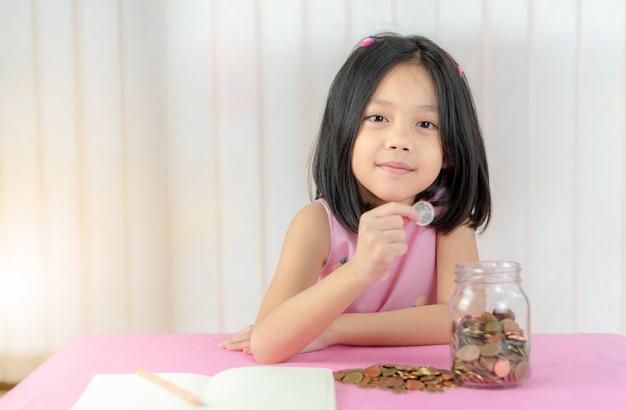 Meisje dat een muntstuk zet in een spaarvarken, het geldconcept van de jong geitjebesparing.