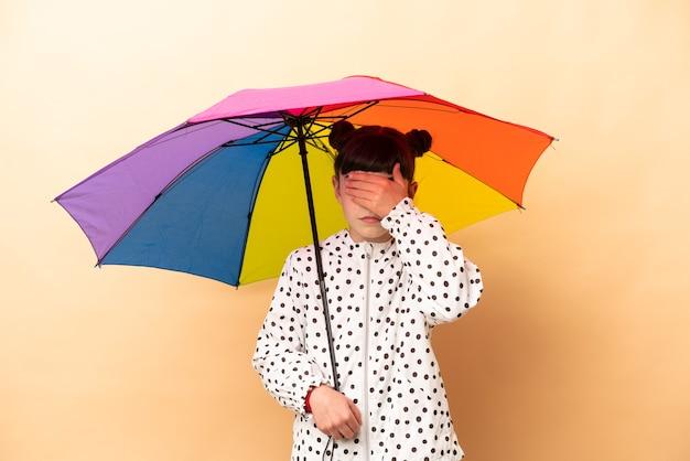 Meisje dat een paraplu houdt die op beige wordt geïsoleerd die ogen behandelt door handen. ik wil niets zien