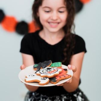 Meisje dat een plaat met koekjes houdt