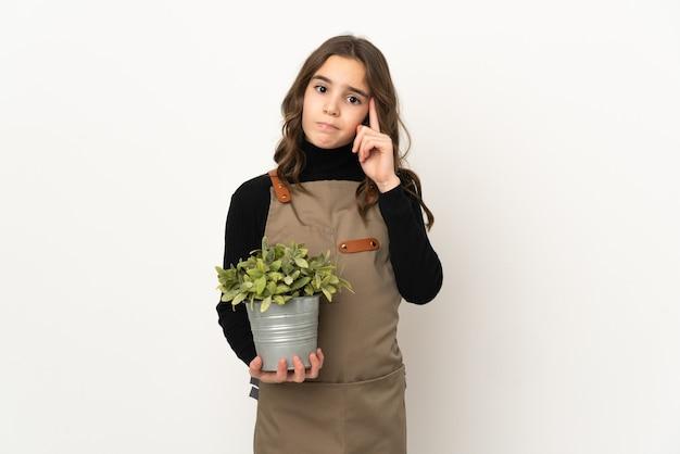 Meisje dat een plant houdt die op witte muur wordt geïsoleerd die een idee denkt