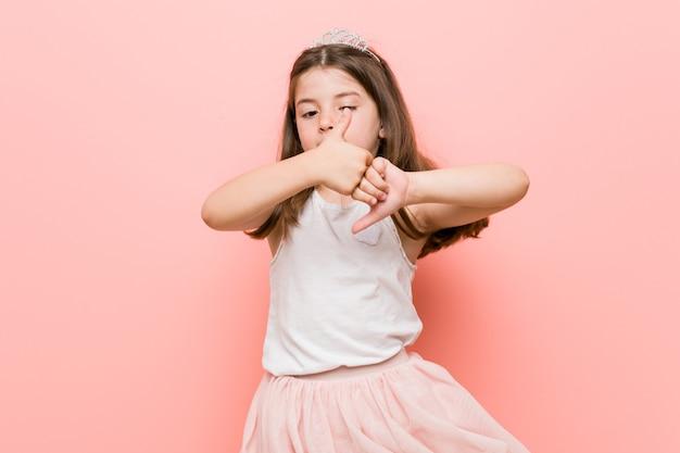 Meisje dat een prinses draagt die een rotsgebaar met vingers toont