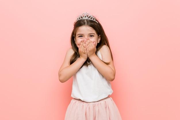 Meisje dat een prinses draagt, lacht om iets, de mond bedekt met handen.