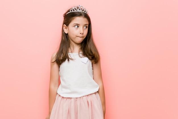 Meisje dat een prinses draagt, ziet er verward uit, voelt zich twijfelachtig en onzeker.