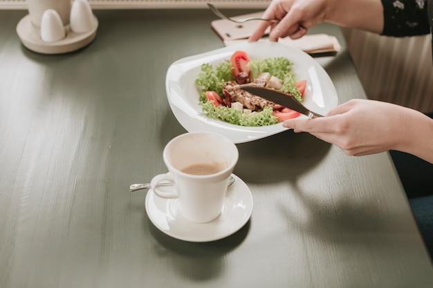 Meisje dat een salade in een restaurant eet