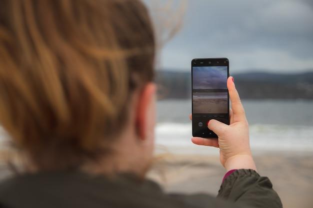 Meisje dat een schot neemt met haar mobiel van de zee