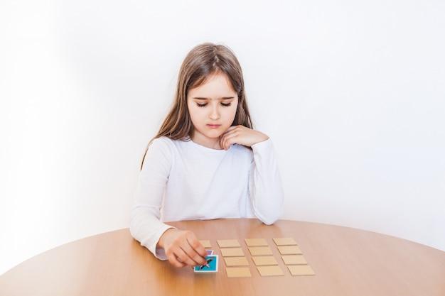Meisje dat een spel speelt, mentale vaardigheid, onthouden, bordspel, spelen tijdens de vakantie, recreatie, isolatie, tijd met voordelen, de geest ontwikkelen