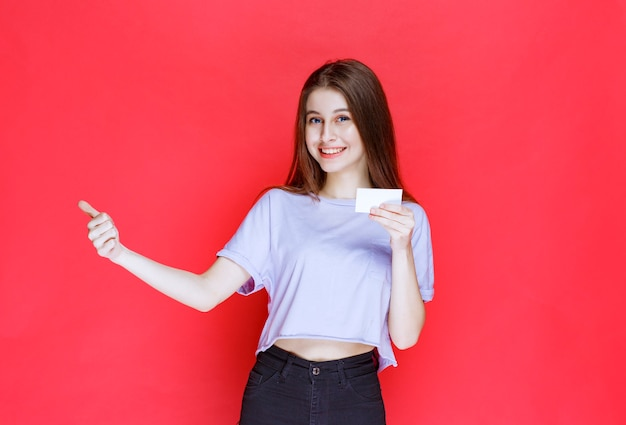 Meisje dat een visitekaartje houdt en positief handteken toont.