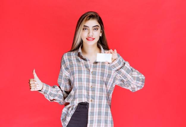 Meisje dat een visitekaartje houdt en tevredenheidsteken toont