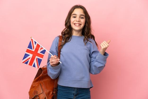 Meisje dat een vlag van het verenigd koninkrijk houdt die op roze achtergrond wordt geïsoleerd die naar de kant wijst om een product te presenteren