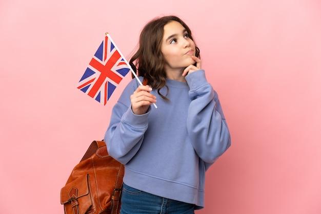 Meisje dat een vlag van het verenigd koninkrijk houdt die op roze achtergrond wordt geïsoleerd die twijfels heeft terwijl het opzoeken