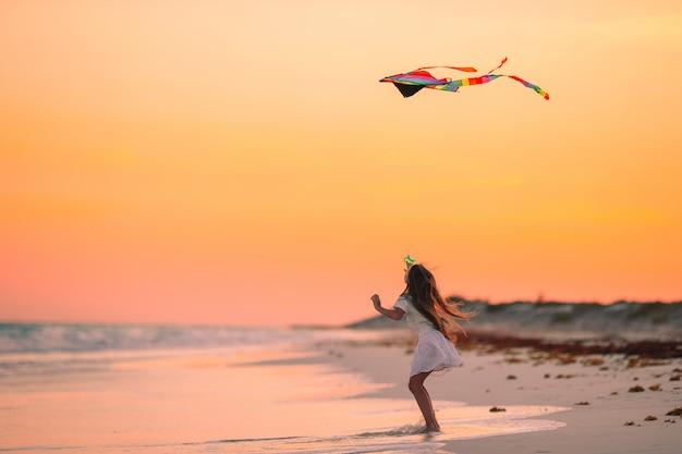 Meisje dat een vlieger op het strand met turkoois water vliegt