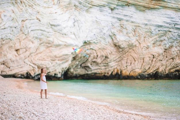 Meisje dat een vlieger op het strand met turquiosewater vliegt