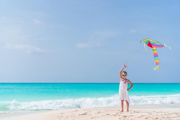 Meisje dat een vlieger op strand vliegt