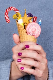 Meisje dat een wafelkop met snoepjes houdt
