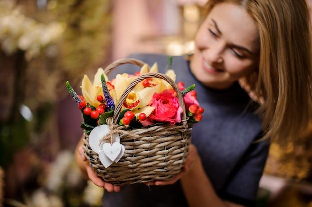 Meisje dat een weinig mooie mand van de lentebloemen houdt