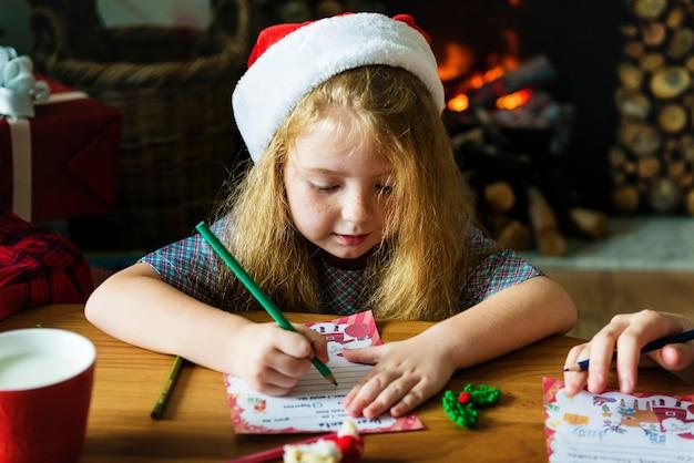 Meisje dat een wenskaart van kerstmis schrijft