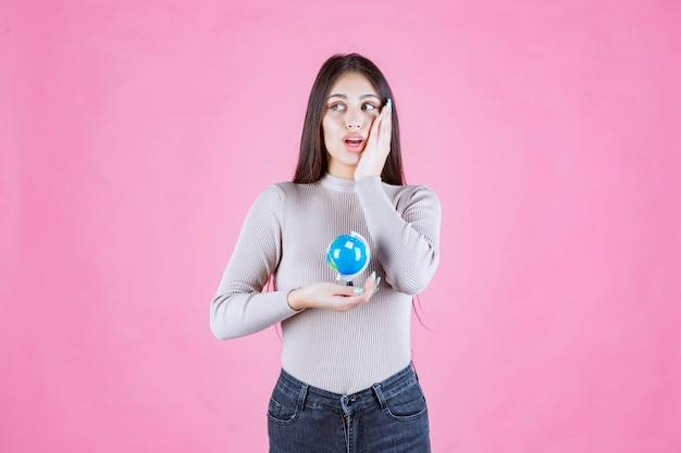 Meisje dat een wereldbol vasthoudt en verrast wordt