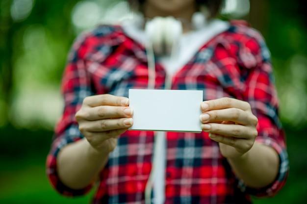 Meisje dat een wit adreskaartje houdt