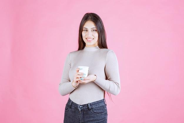 Meisje dat een wit wegwerpkoffiekopje houdt, het promoot of de verse koffie ruikt