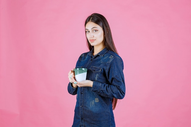 Meisje dat een witgroene koffiemok houdt en ruikt