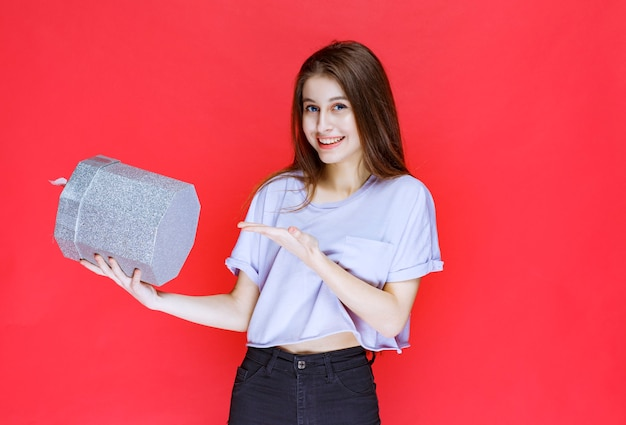 Meisje dat een zilveren geschenkdoos vasthoudt en promoot.
