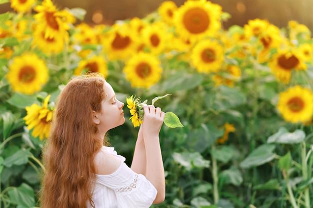 Meisje dat een zonnebloem ruikt