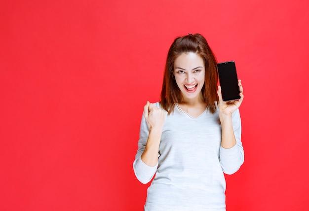 Meisje dat een zwarte smartphone houdt en positief handteken toont.