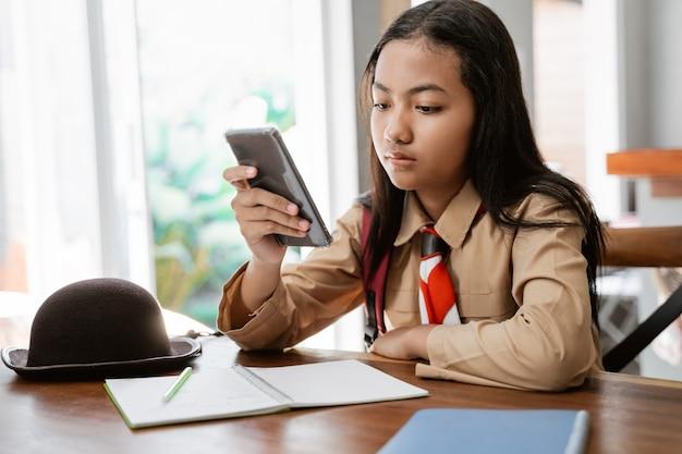 Meisje dat eenvormige verkenner draagt die en mobiele telefoon bestudeert gebruikt